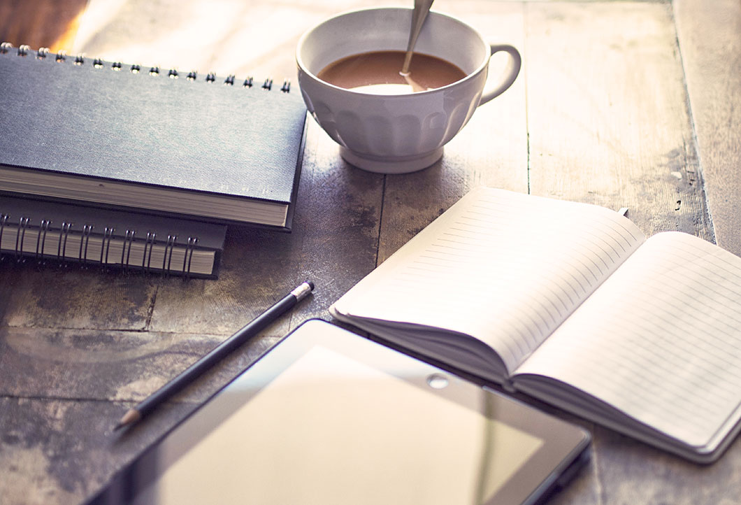 Zdjęcie przedstawiające notesy, kawę i tablet na stole
