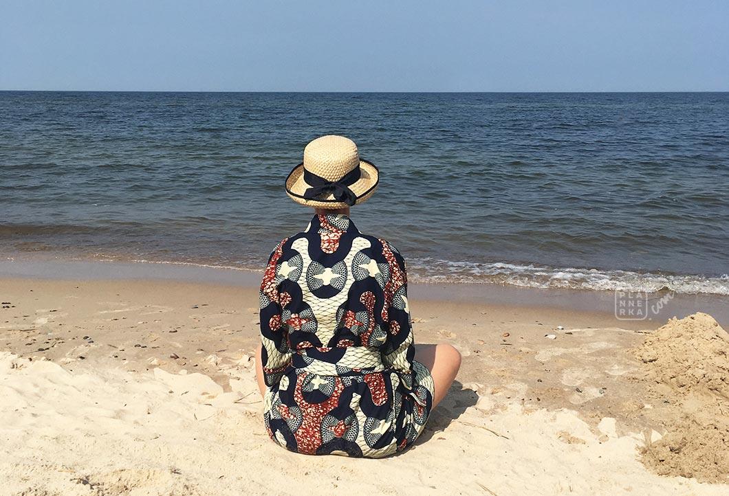 Pokazana od tyłu sylwetka osoby siedzącej na plaży, patrzącej w stronę morz