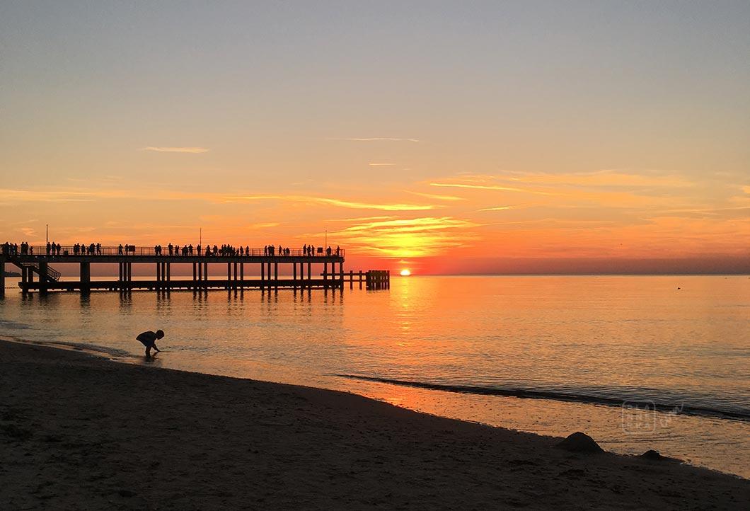 Widok molo i morza na tle zachodzącego słońca