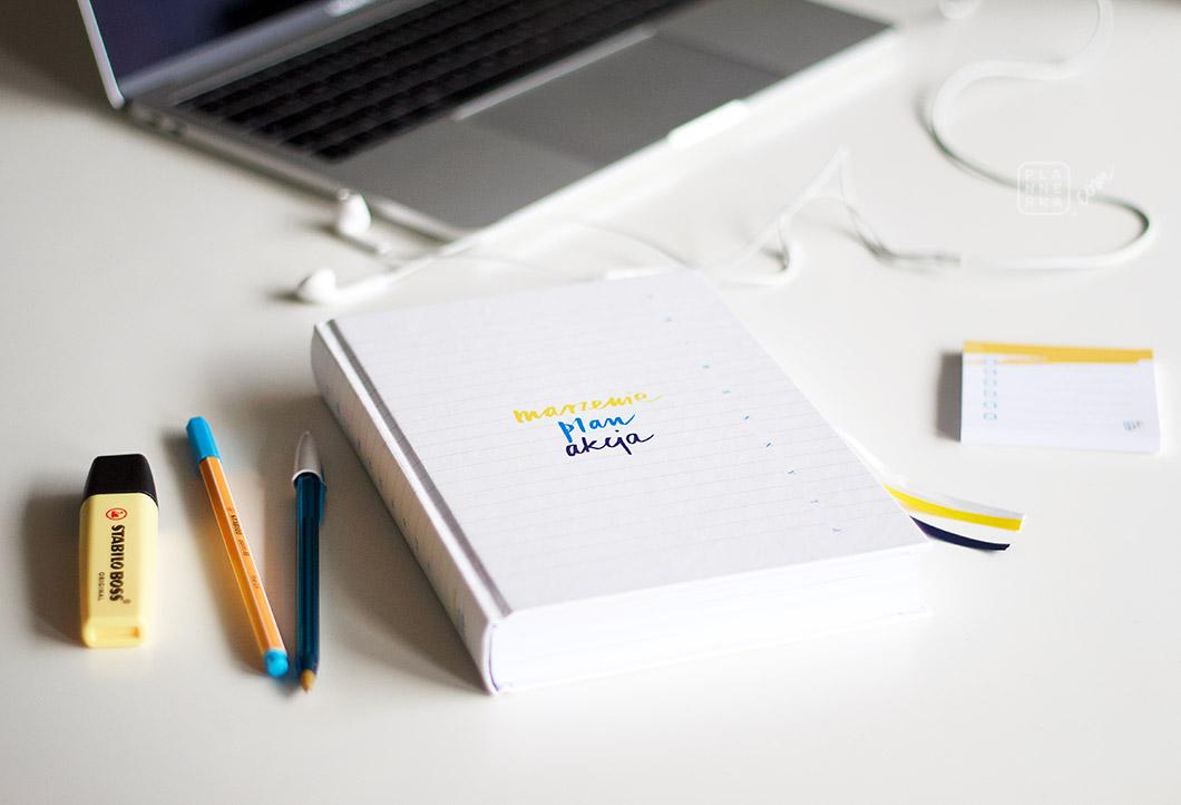 Planner, długopisy i komputer na biurku