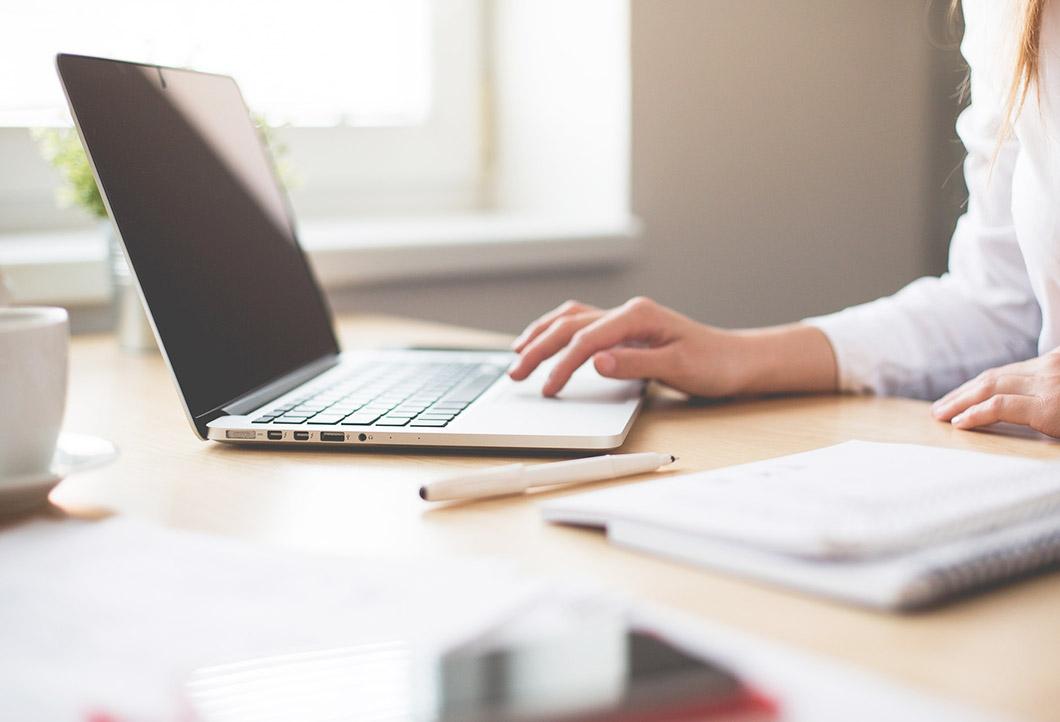 Zdjęcie dłoni kobiety pracującej na laptopie